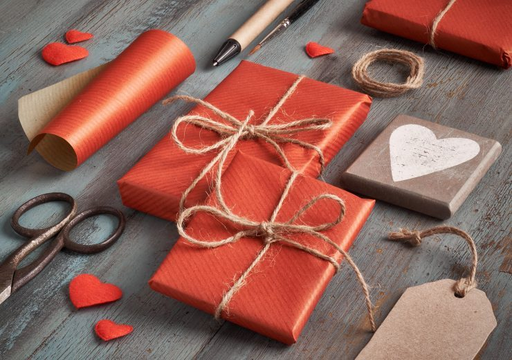 Packed presents, paper, cord and labels onrustic wooden table